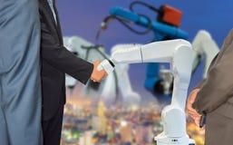 与机器人机器人胳膊未来产业4的商人握手的合作 库存照片