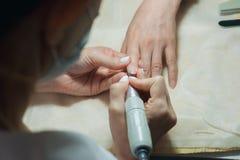 与机器的Profesional钉子技术员铺沙的钉子 免版税库存照片