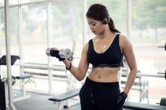 年轻与机器缆绳天桥的健身亚洲妇女锻炼 免版税库存图片