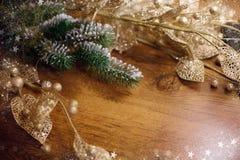 与杉木分支发光的金黄装饰和新年的闪亮金属片火焰bokeh的圣诞节背景 库存图片