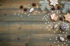 与杉木锥体、姜饼曲奇饼和冷杉的圣诞节或新年构成在木背景 平的位置,顶视图 免版税库存图片