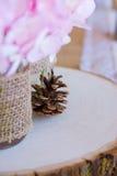 与杉木锥体和桃红色花的婚礼装饰 免版税库存照片