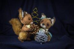 与杉木锥体的两只灰鼠在一棵装饰树附近 免版税图库摄影