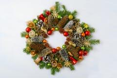 与杉木锥体,红色和金黄装饰品的圣诞节花圈 免版税图库摄影
