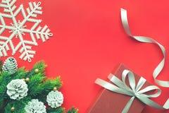 与杉树、杉木分支、雪和红色背景的圣诞节装饰品 库存图片