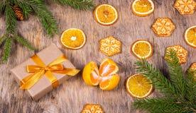 与杉树、礼物盒、曲奇饼、雪花和蜜桔的圣诞节装饰 弓金黄配件箱的礼品 库存照片