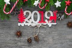 2019与杉树、糖果和装饰的新年快乐木数字在木桌上 顶视图 免版税库存照片