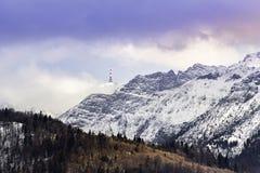 与杉树、雪、云彩和无线电天线的山脉 图库摄影