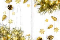 与杉树的圣诞节框架分支,圣诞灯、杉木锥体和金黄装饰品在白色木背景 图库摄影