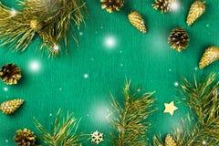 与杉树的圣诞节框架分支,杉木锥体和金黄装饰品在温暖的绿色背景,雪落 免版税库存图片