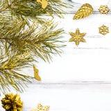 与杉树的圣诞节框架分支,杉木锥体和金黄装饰品在白色木背景,拷贝空间 免版税库存照片