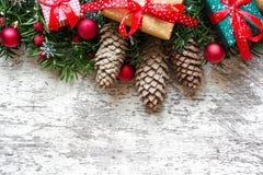 与杉树的圣诞节背景分支,装饰和礼物盒在白色木板 库存图片