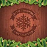 与杉树的被刻记的圣诞快乐和新年快乐印刷设计在木纹理背景 免版税图库摄影
