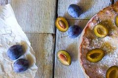 与李子装填和果酱的新鲜和温暖的蛋糕 馅饼装饰用搽粉的糖 热,甜面团 土气木桌 A 库存图片