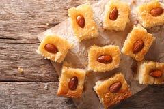 与杏仁basbousa的蛋糕在纸 水平的顶视图 免版税库存图片