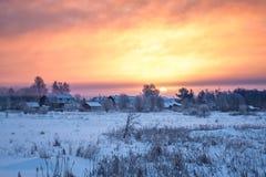 与村庄、日出和雾的冬天农村风景 免版税库存照片
