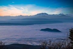 与杜富尔峰的高山链子从云彩海涌现在日落 从园地dei瓦雷泽,意大利Fiori的鸟瞰图  免版税库存照片