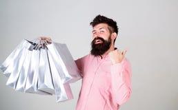 与束纸袋的愉快的购物 有益的交易 购物的上瘾的消费者 总销售概念 有胡子的人 免版税库存图片