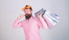 与束纸袋的愉快的购物 购物的上瘾的消费者 人有胡子的行家穿戴太阳镜举行束 免版税库存图片