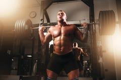 与杠铃的举重运动员锻炼在体育健身房 库存图片