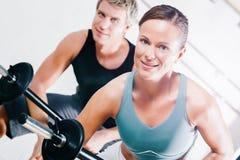 与杠铃的力量体操在健身房 免版税库存照片