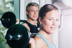 与杠铃的力量体操在健身房 免版税库存图片
