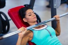 与杠铃的妇女锻炼在长凳 库存图片