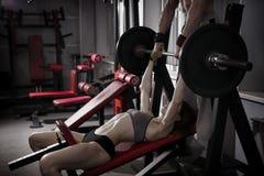 与杠铃的性感的健身女孩锻炼在健身房 体育穿戴的深色的妇女与完善的强健的身体 库存照片