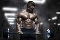 与杠铃的残酷运动肌肉爱好健美者锻炼在健身房 免版税库存图片