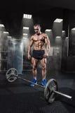 与杠铃的肌肉人锻炼在健身房 Deadlift杠铃工作 免版税库存图片