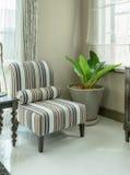 与条纹图形的典雅的客厅内部在扶手椅子把枕在 免版税库存图片