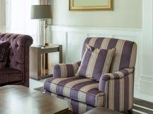 与条纹图形的典雅的客厅内部在胳膊把枕在 图库摄影