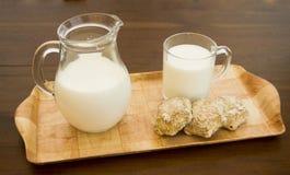 与杯子和一个水罐的木盘牛奶 免版税库存照片