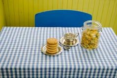 与杯子和曲奇饼的干万寿菊盘在桌上 免版税库存图片
