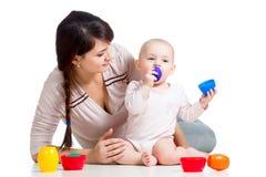 与杯子玩具一起开玩笑女孩和母亲作用 库存图片