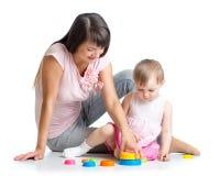 与杯子玩具一起开玩笑女孩和母亲作用 免版税图库摄影