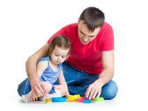 与杯子玩具一起的孩子和父亲戏剧 免版税库存照片