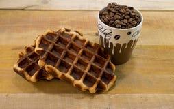 与杯子的两个新鲜的奶蛋烘饼有很多咖啡豆 图库摄影