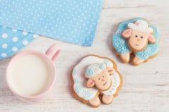 与杯子的两只逗人喜爱的姜饼绵羊牛奶 库存照片