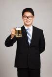 与杯子的亚洲商人啤酒 免版税库存图片