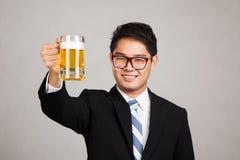 与杯子的亚洲商人欢呼啤酒 库存图片