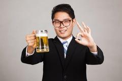 与杯子的亚洲商人OK啤酒 库存照片