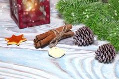 与杯子的圣诞节装饰热的可可粉,有蜡烛的,肉桂条,杉木,在木浅兰的桌上的冷杉分支灯 平面 免版税库存照片