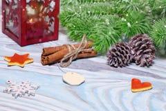 与杯子的圣诞节装饰热的可可粉,有蜡烛的,肉桂条,杉木,在木浅兰的桌上的冷杉分支灯 平面 图库摄影
