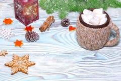 与杯子的圣诞节装饰热的可可粉,有蜡烛的,肉桂条,杉木,在木浅兰的桌上的冷杉分支灯 平面 免版税库存图片