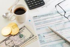 与杯子的收入税单形式浓咖啡、金钱、笔、计算器和玻璃 免版税库存图片