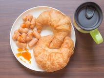 与杯子的新月形面包和心脏香肠在木桌上 库存图片