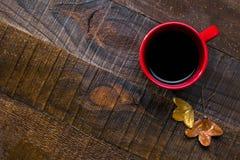 与杯子的秋天静物画无奶咖啡和叶子在老湿木桌上 平的位置 免版税库存图片