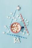 与杯子的艺术构成热的可可粉或巧克力和在蓝色背景顶视图的风格化杉树 袋子看板卡圣诞节霜klaus ・圣诞老人天空 平的位置 免版税库存照片