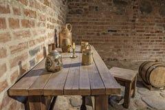 与杯子的表在葡萄酒库里 免版税库存图片